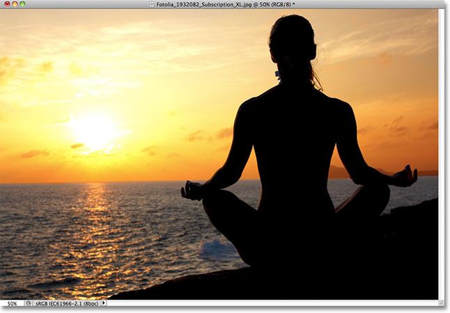 Женщина медитирует на закате.  Изображение лицензировано от Fotolia фотошопом Essentials.com.
