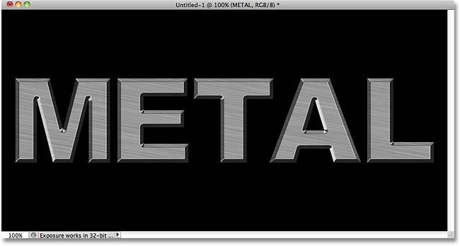 Металлический текст с нанесенными Bevel и Emboss.  Image © 2010 Photoshop Essentials.com.