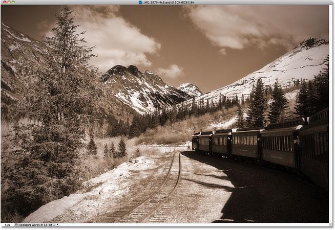 Сепия тонированное фото поезда, уходящего в горы.