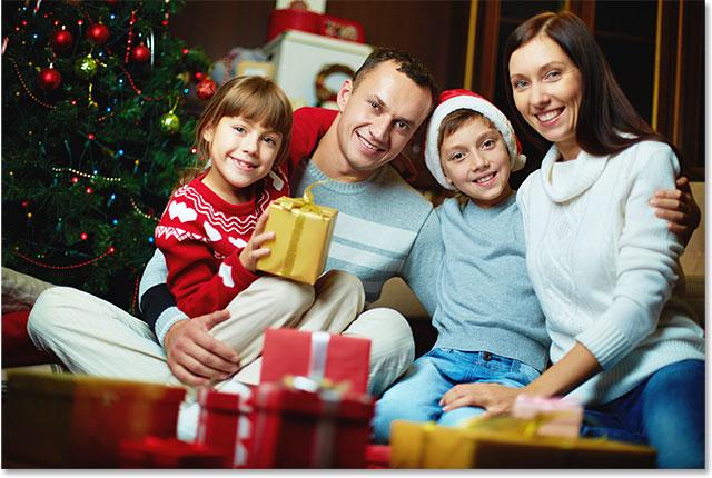 Портрет дружной семьи, глядя на камеру на Рождественский вечер.  Изображение 115748269 лицензировано от Shutterstock Photoshop Essentials.com