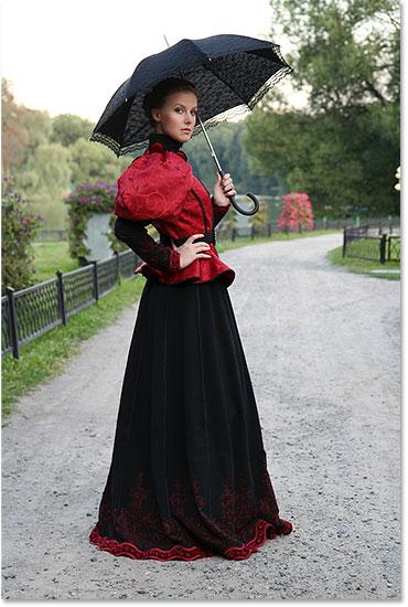 Девушка с зонтиком в винтажном костюме в парке.  Изображение лицензировано от Shutterstock фотошопом Essentials.com.  Не использовать без разрешения.